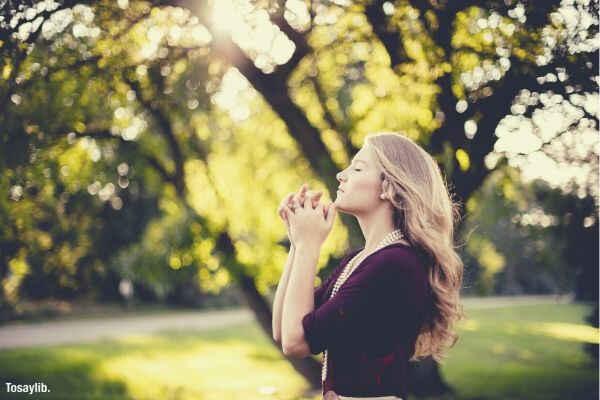 woman praying tree day time grass
