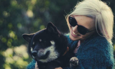 woman-sunglass-bluegreen-coat-holding-black-dog