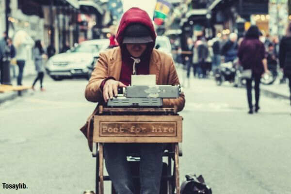 man sitting typing on a type writer middle of street