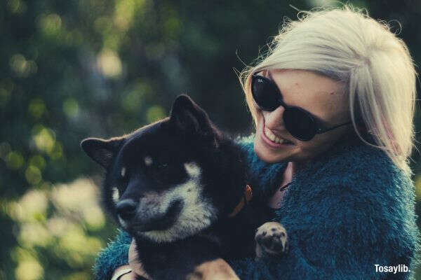 woman sunglass bluegreen coat holding black dog
