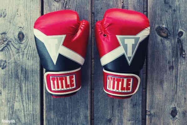 pair black red white title gloves on gray wooden plank