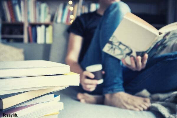 reading a book and having a coffee on couch person books