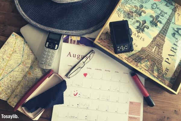 calendar glass hat camera pen cellphone map on table