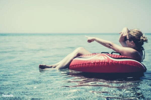 woman pointing ocean riding inflatable float sky