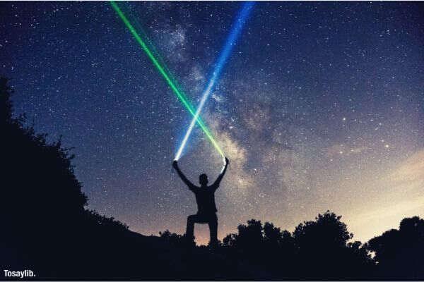 peson holding green blue lights night star sky