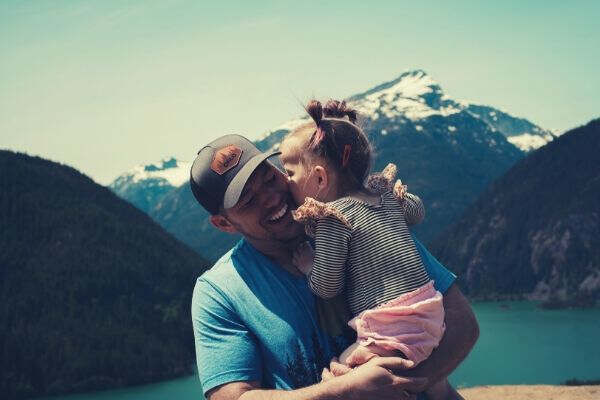 man-carrying-her-daughter-smiling-mountains-lake