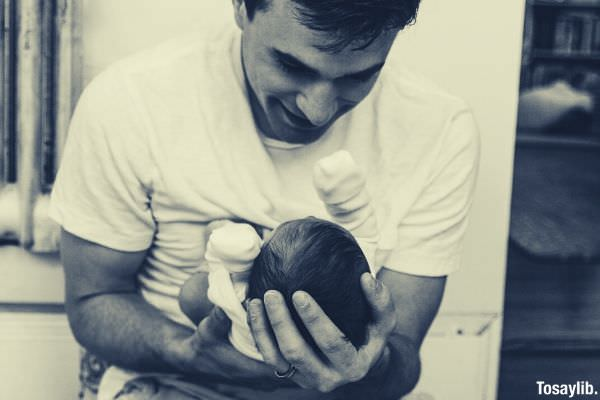 man holding a baby black and white