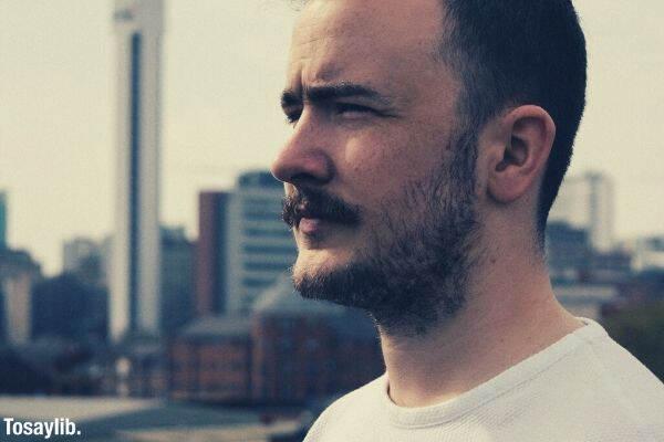 man beard white shirt taking photo