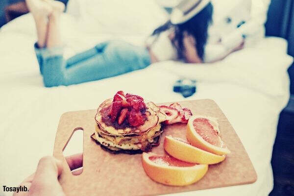 selective focus person holding tray of foods woman lying on bed