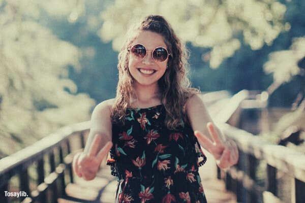 woman smiling peace sign sunglasses bridge tree