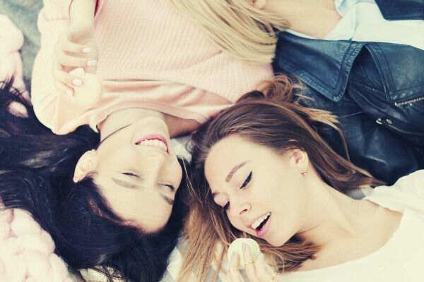 three-woman-lying-smiling-eating-macaroons