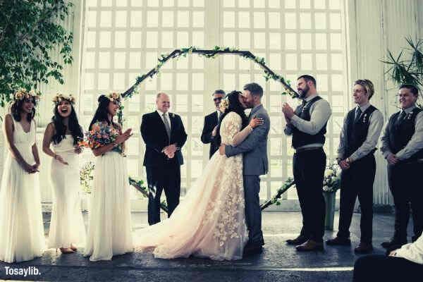 bride groom kissing people guest happy large window