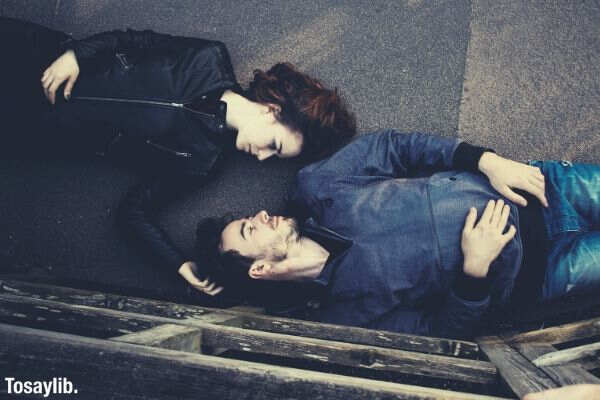 man and woman lying on concrete surface