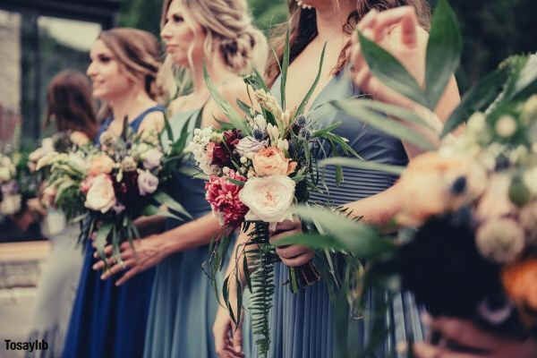 selective focus photography of women holding wedding flowers blue gray gown