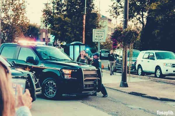 people standing beside black pickup truck