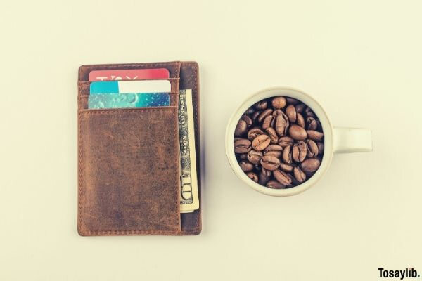 white mug with coffee beans beside brown wallet