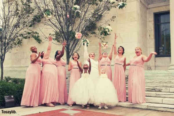 women wearing dresses while throwing bouquets pink motif