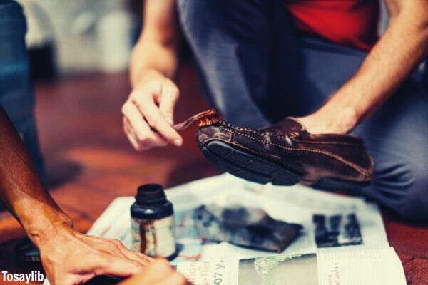 person brushing brown dress shoe