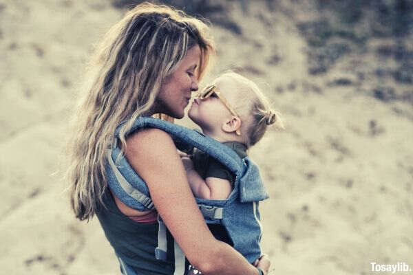 woman carrying girl while kissing