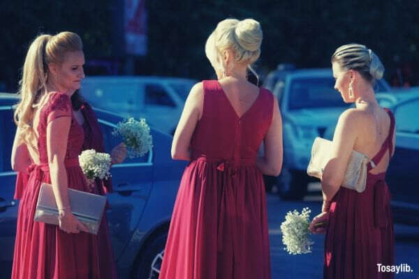 three women facing each other red gown cars