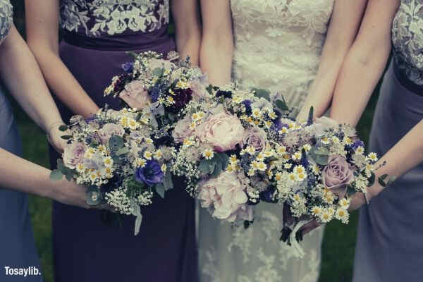 picture of four women holding bouquet pink purple