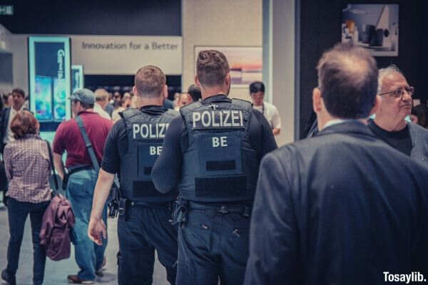 men polizei officers standing in front of people