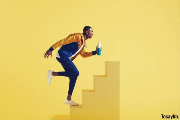 L3 man in blue pants and yellow jacket running on stairs