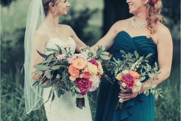 bride-bridesmaid-smiling-each-other-holding-bouquet-grass