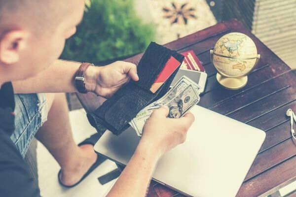 man-holding-u-s-dollar-banknotes-and-black-leather-bi-fold-wallet-laptop-globe-wooden-table