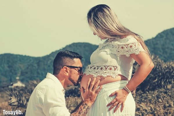 man wearing white dress shirt kissing woman on her baby bump
