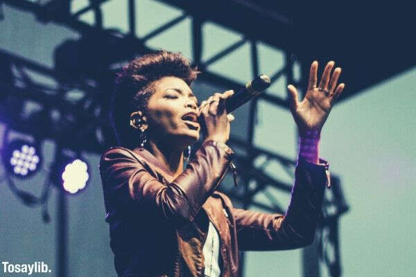 woman raising her hand while singing