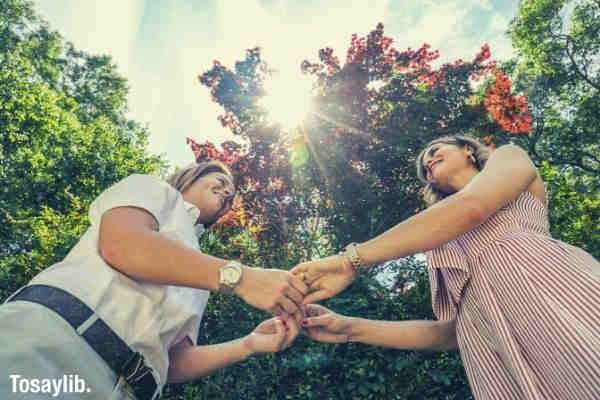 two women holding hands sunlight trees