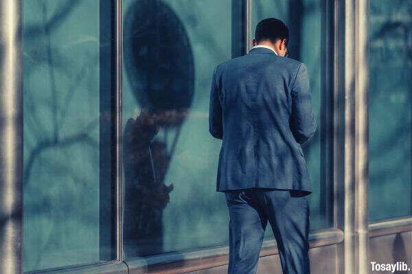 man walking near glass wall