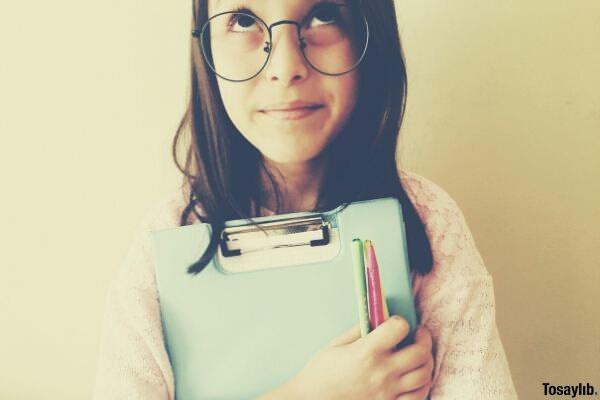 girl in eyeglasses holding paperworks
