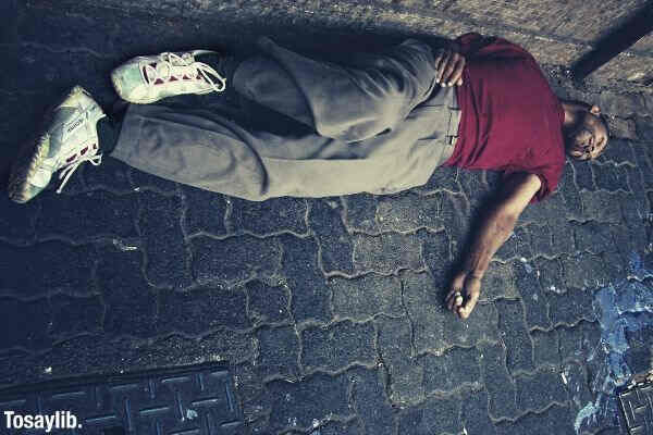 man in red shirt lying on the ground