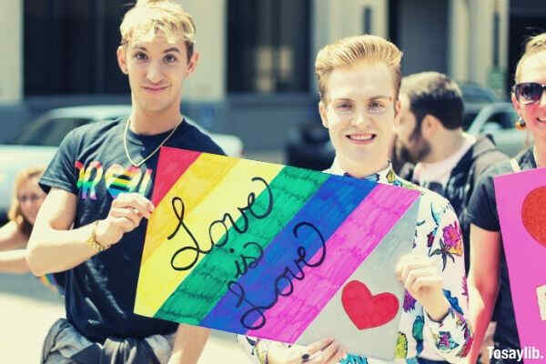 two gays holding assorted painted love is love banner