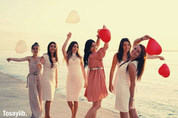 group of women holding balloons sea