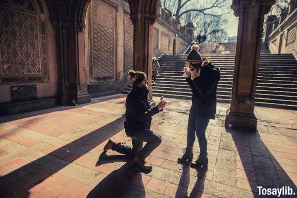 man on one knee proposing to a woman staircase