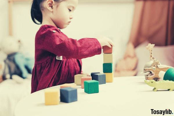 selective focus side view photo of young girl in red long sleeve dress playing with building blocks