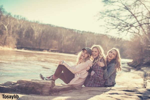 three woman sitting on rock smiling river trees