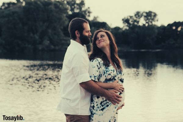 husband hugging pregnant wife smiling river trees