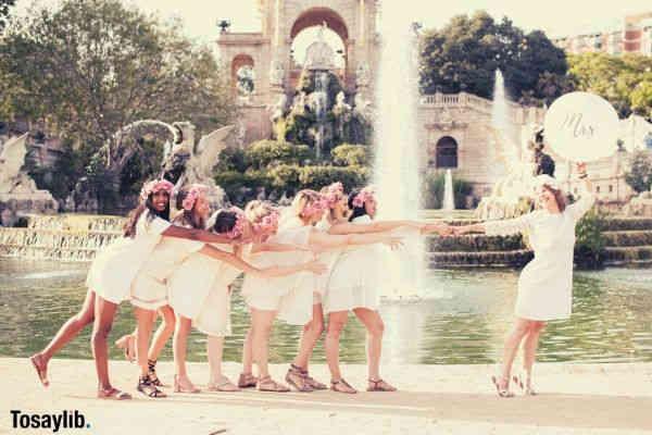bride holding mrs bridesmaids near fountain architecture