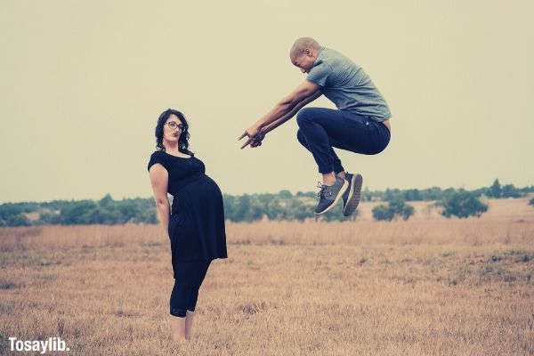 man jumping pointing on womans baby bump grass sky