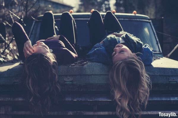 03 photo of two women lying on the vehicle