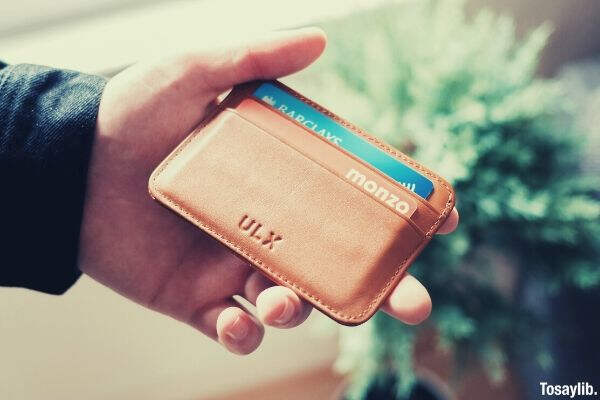 person holding brown leather ULX wallet