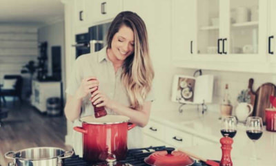 smiling-woman-standing-putting-pepper-on-stock