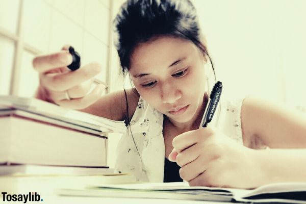 woman studying writing in her notebook