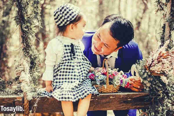 man holding a bouquet of flower while looking at the baby girl