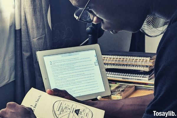 black man with eyeglass reading a book