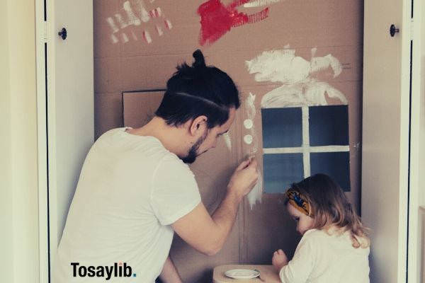 man in white shirt and brown pants painting cardboard house with daughter